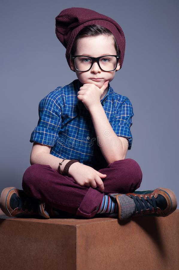 The modern kid wearing spectacles poses on a gray background. A boy is sitting with so serious face. He is wearing plaid shirt and. Burgundy pants with hat stock photos