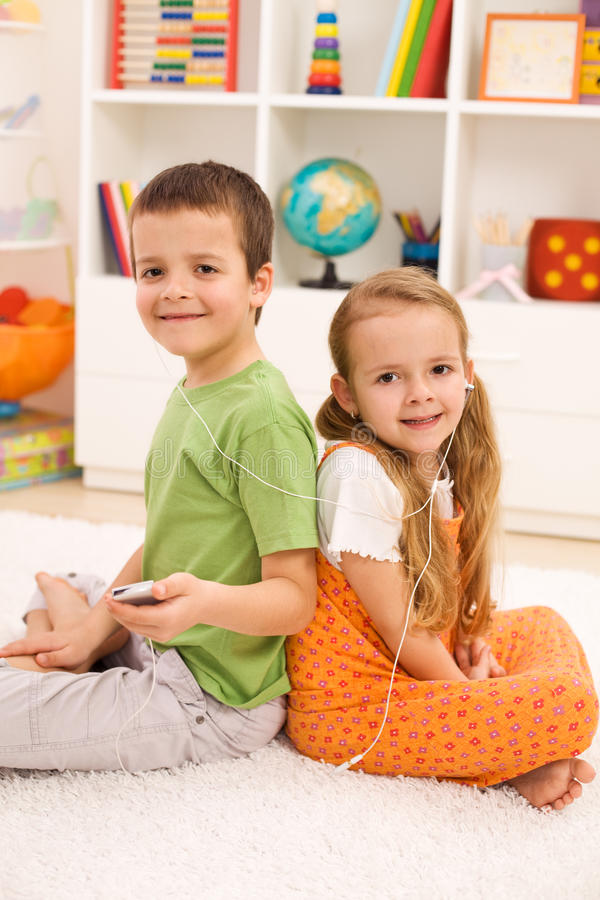 Modern kids listening to music in their room stock image