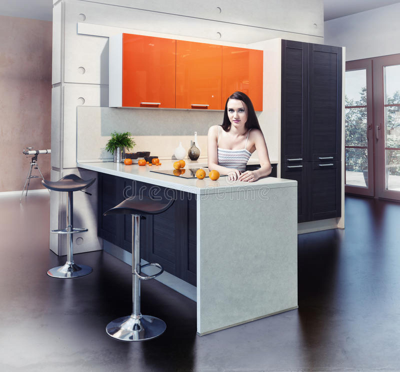 Modern kitchen. Young beautiful woman in kitchen interior stock photo
