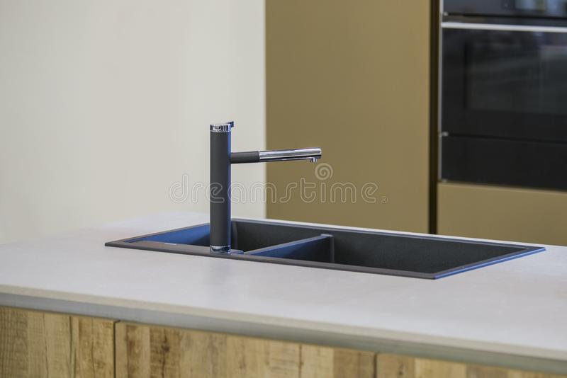 Modern kitchen, the black water tap and kitchen sink. Kitchen island with a tap and gray worktop.  stock image