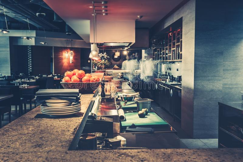 Modern kitchen and chefs in restaurant. Restaurant kitchen interior: bar counter made of natural stone, fences off the open kitchen and hall for visitors with stock photos