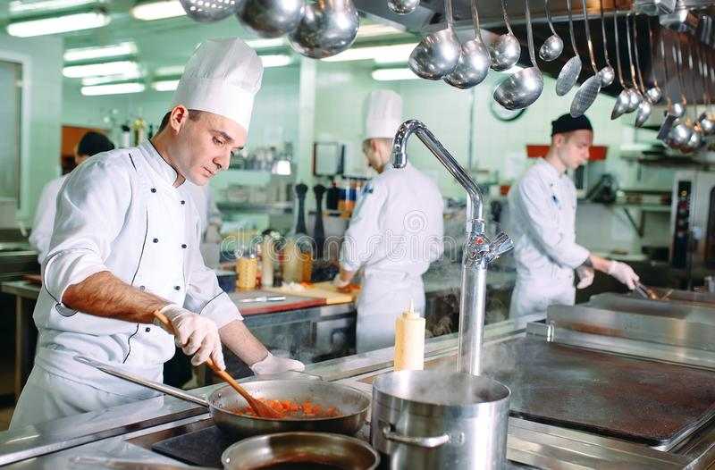 Modern kitchen. Cooks prepare meals on the stove in the kitchen of the restaurant or hotel. The fire in the kitchen. stock photos