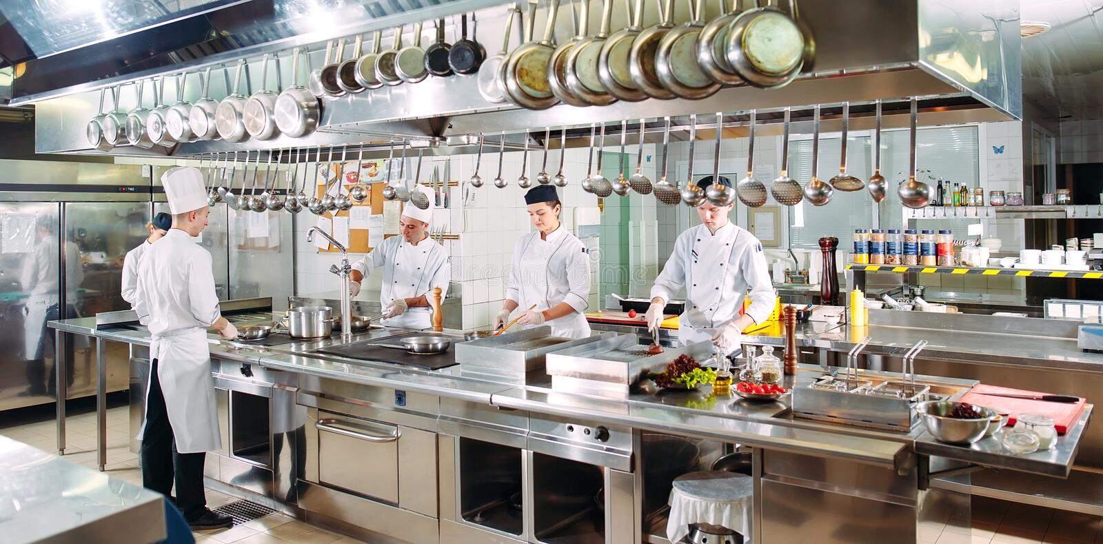 Modern kitchen. Cooks prepare meals on the stove in the kitchen of the restaurant or hotel. The fire in the kitchen. Modern kitchen. Cooks prepare meals on the stock photography