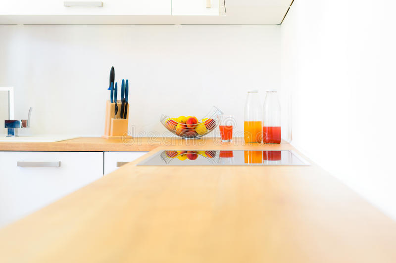 Modern kitchen counter with induction hob, fresh fruit and homemade lemonade stock photo