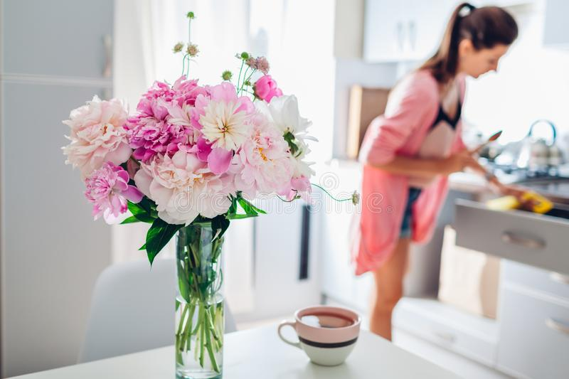 Modern kitchen decorated with pink peonies. Housewife cooking dinner. Interior design royalty free stock photo