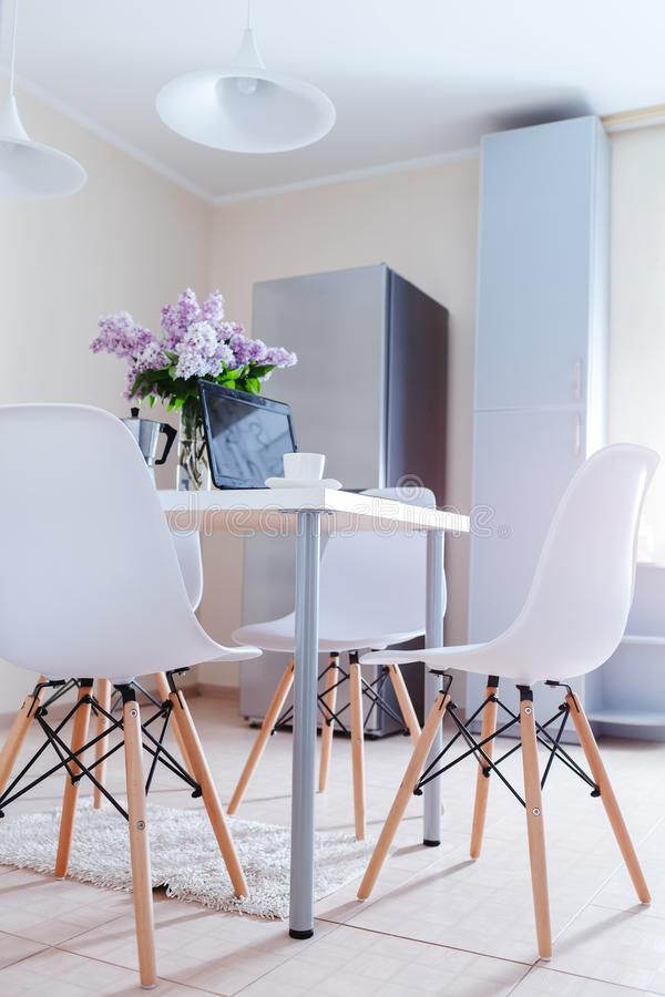 Modern kitchen design. Interior of light dining room decorated with lilac flowers. Laptop and coffee on table stock photos