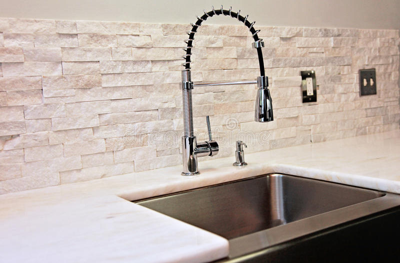 Modern kitchen detail. A modern kitchen sink, marble counter and stacked stone back splash and industrial spray faucet royalty free stock photos