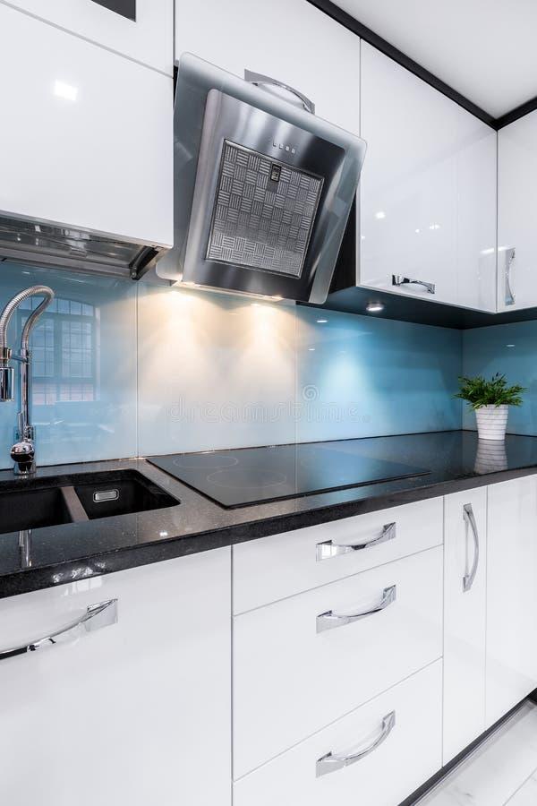 Modern kitchen interior with new furniture. Luxury kitchen interior with modern white furniture and black kitchen worktop royalty free stock images