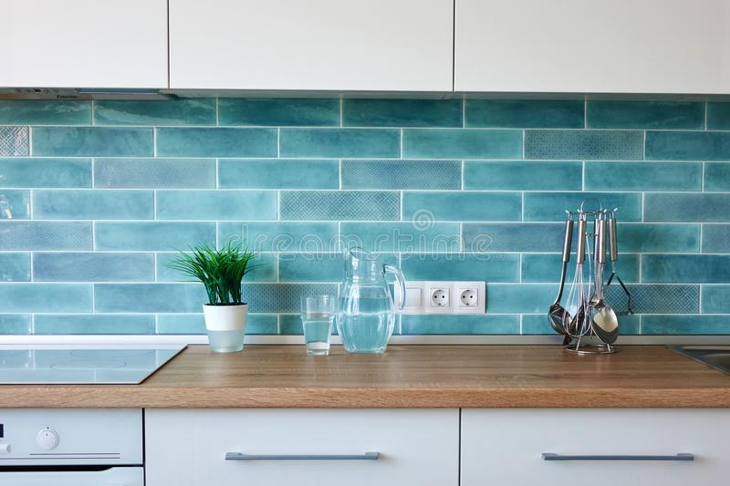 Modern kitchen at home with kitchenware. Modern white kitchen at home with utensils on the background of blue tiles royalty free stock images