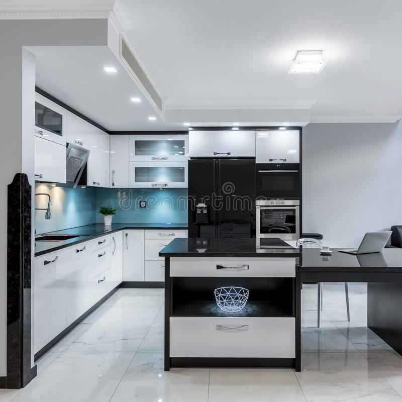 Luxury kitchen space with island. Modern and luxury black and white kitchen space with island royalty free stock photos