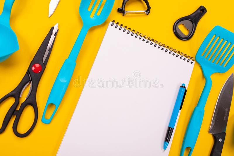 Top view of a clean sheet and kitchen utensils next to it isolated on a yellow background. Modern kitchen tools and a clean white sheet between them isolated on stock photo
