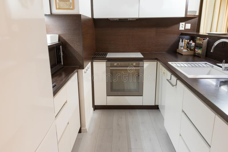 Modern kitchen in white and brown color design royalty free stock image