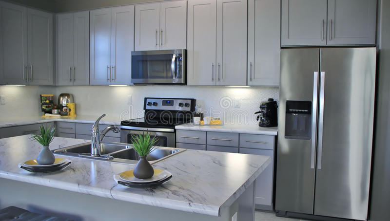 Modern Kitchen in White. Modern high end luxury kitchen in new construction home with a marble island royalty free stock images