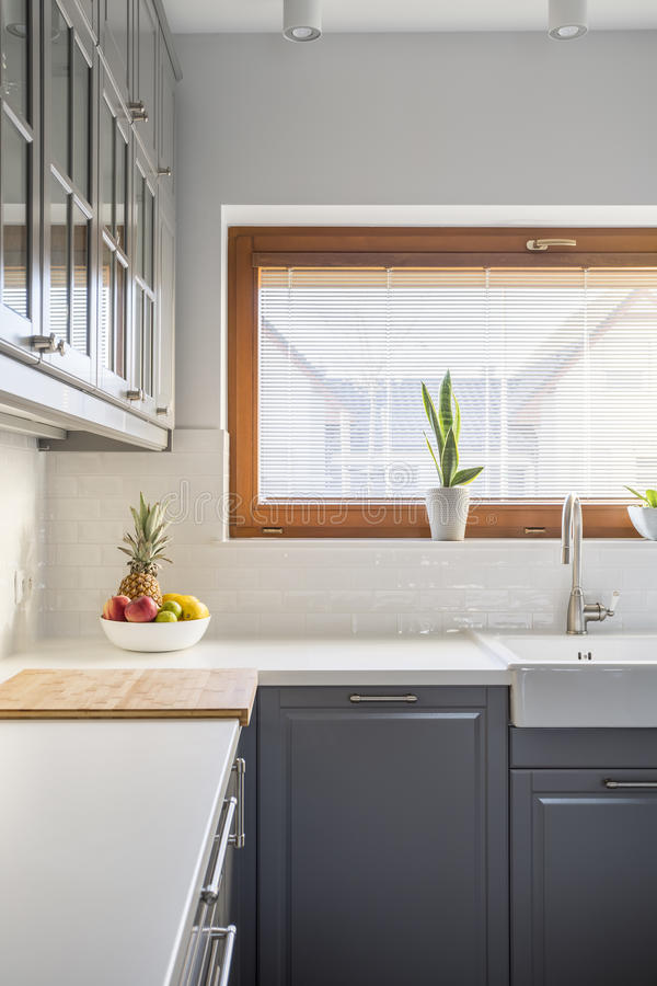 Modern kitchen with window. Grey cupboard, white countertop and sink royalty free stock images