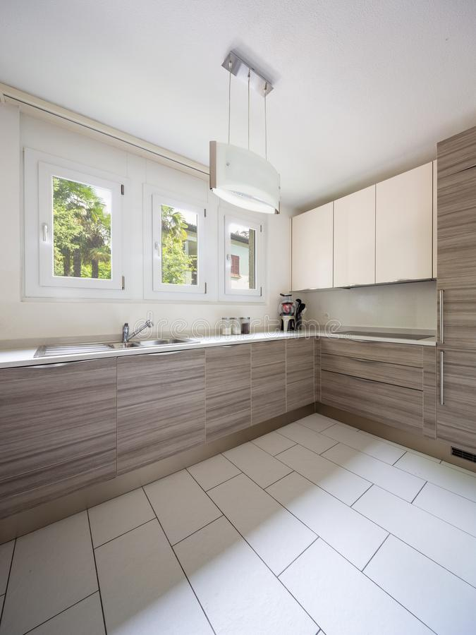 Modern kitchen with wood and a window where a lot of light enters. Nobody inside royalty free stock photo