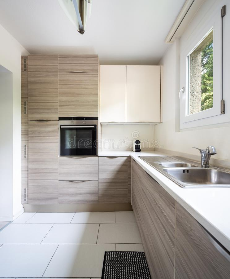 Modern kitchen with wood and a window where a lot of light enters. Nobody inside stock images