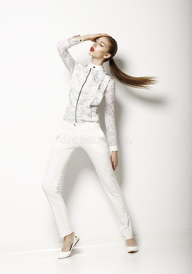 Modern kläddesign. Modern kvinna i den vita blusen och flåsanden. Mode arkivbild