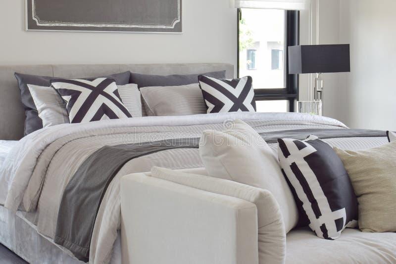 Modern klassiek stijlbeddegoed met comfortabele bank in bedroo stock afbeeldingen