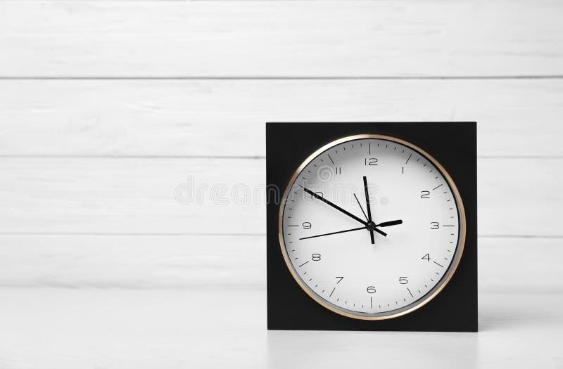 Modern klocka på tabellen mot ljus bakgrund royaltyfri bild