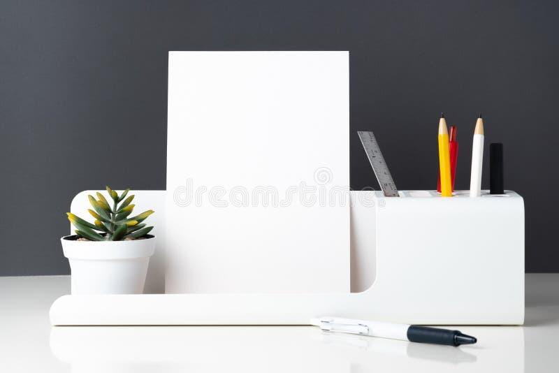 Modern kontorsbrevpapper på den vita tabellen och mörkergrå färgväggen Penci royaltyfri bild