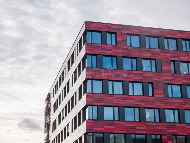 Modern kontorsbyggnad för låg löneförhöjning med den röda fasaden royaltyfri bild