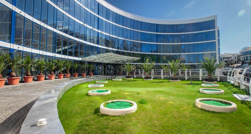 Modern kontorsbyggnad med en exponeringsglasfasad och en grön gräsmatta royaltyfri foto