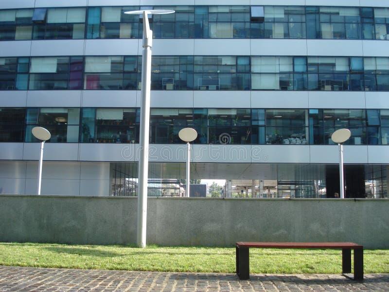 Modern kontorsbyggnad med utomhus- område för avkoppling under arbetsavbrott: royaltyfri bild