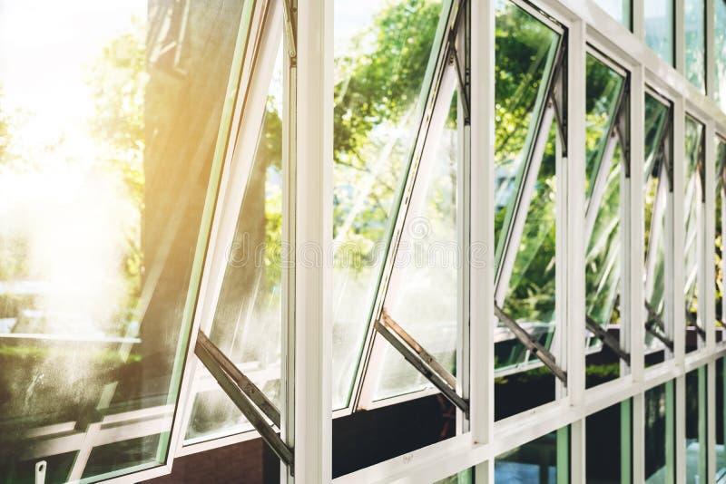 Modern kontorsbyggnadvägg och öppnat fönster i morgonen, med ljust solljus royaltyfri fotografi