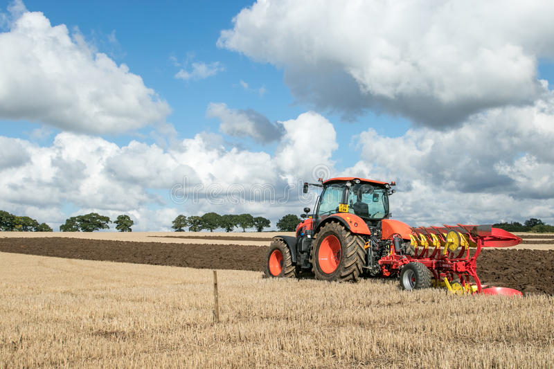 Modern Kubota tractor pulling a plough. Orange modern Kubota tractor ploughing a field with plough working field at ploughing match royalty free stock photography