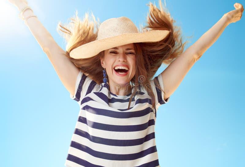 Modern kvinna i fröjd för sugrörhatt mot blå himmel arkivfoton