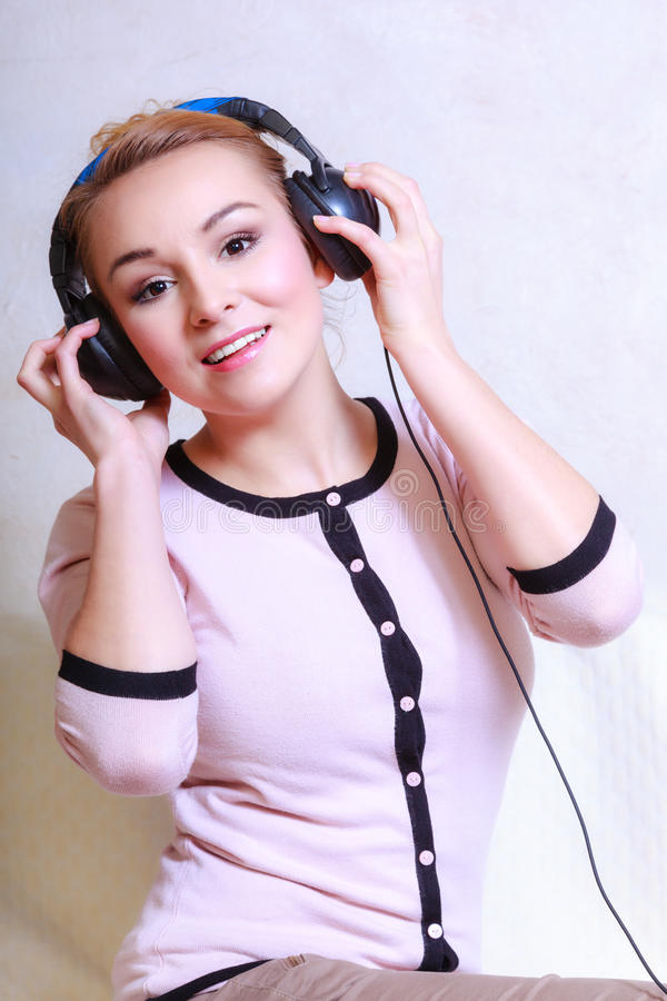 Modern kvinna med hörlurar som lyssnar till musik royaltyfri fotografi