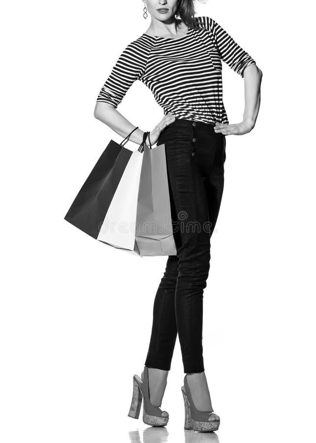 Modern kvinna med shoppingpåsar på vit bakgrund royaltyfria bilder