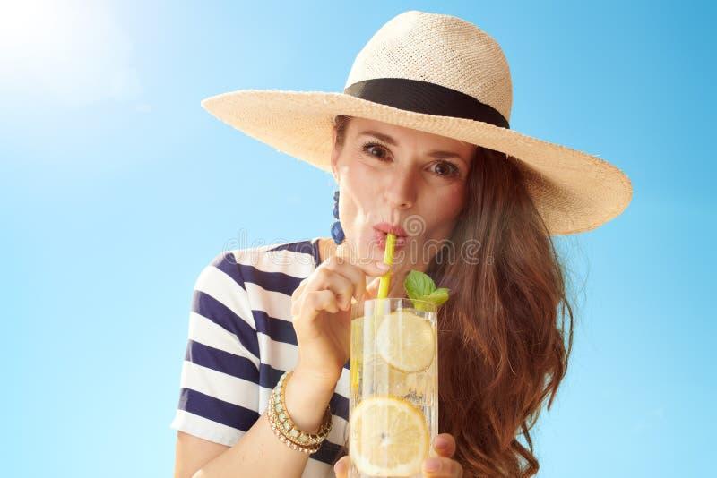 Modern kvinna mot blå himmel som dricker den uppfriskande coctailen royaltyfri fotografi
