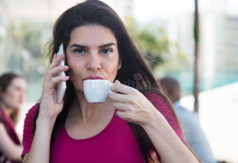 Modern kvinna som talar på telefonen i en restaurang royaltyfri foto