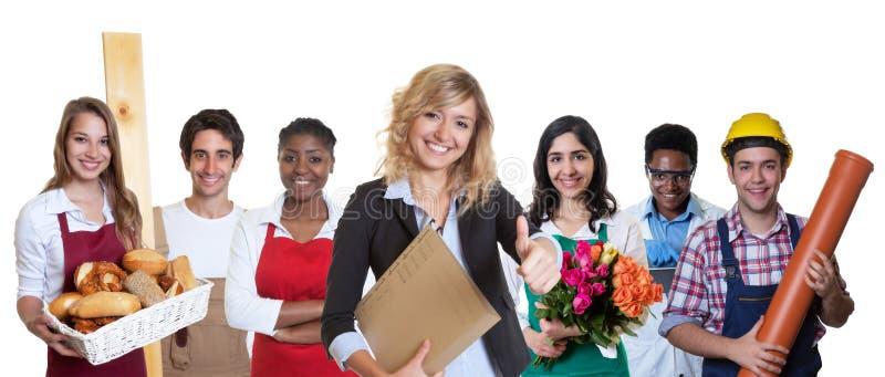 Modern kvinnlig affärsdeltagare i utbildning med gruppen av andra internationella lärlingar royaltyfri foto