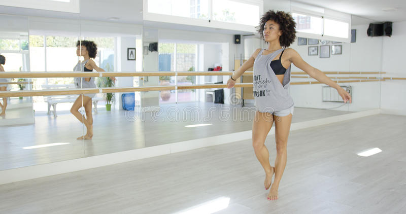 Modern kvinnlig dansare i ljus studioövning arkivbild