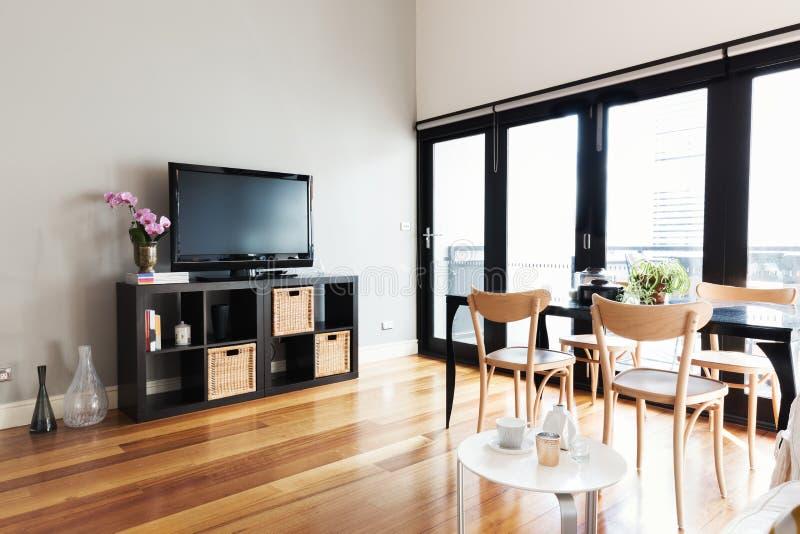 Modern lägenhetvardagsrum med biveckdörren till balkongen royaltyfri fotografi