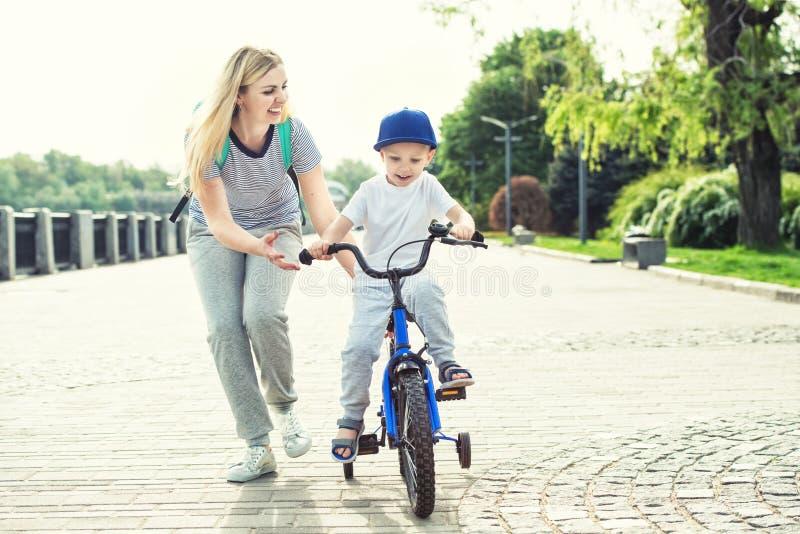 Modern lär hans lilla son för att rida en cykel royaltyfri foto