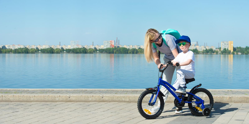 Modern lär hans lilla son för att rida en cykel royaltyfri fotografi
