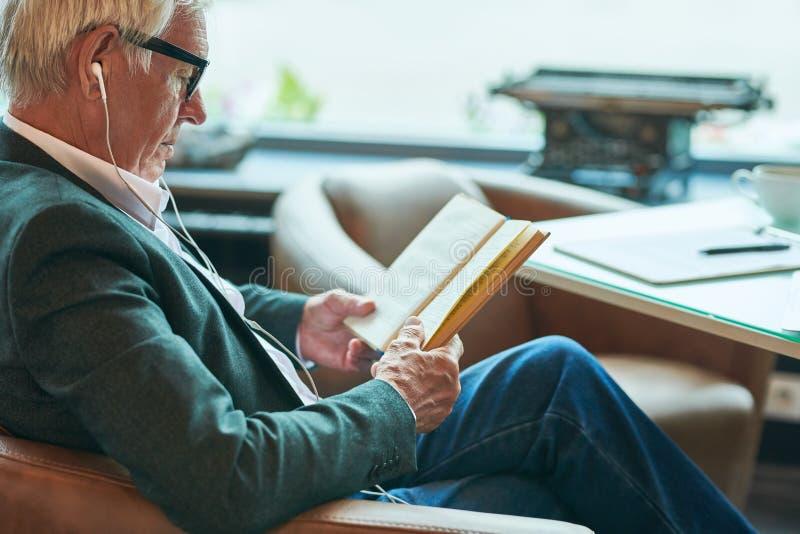 Modern läsning för hög man i kafé fotografering för bildbyråer