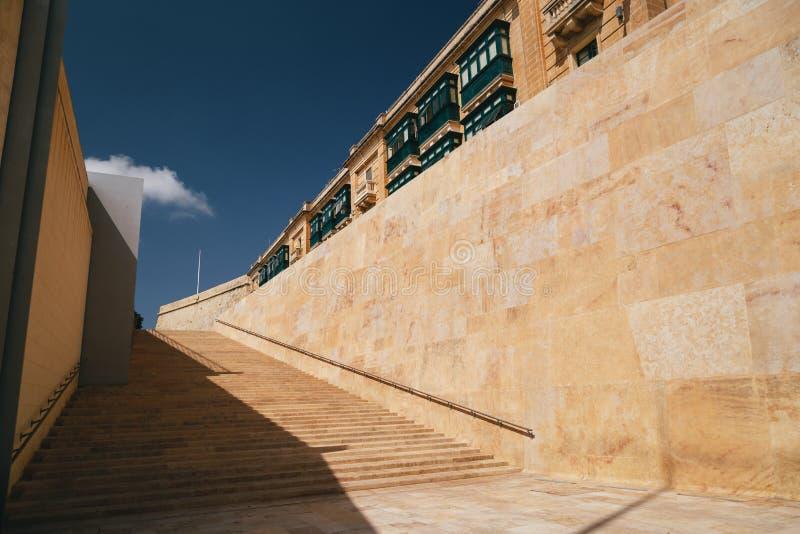 Modern lång trappa från den gula stenen nära till den Valletta stadsporten i Malta och mörkt - blå himmel på bakgrunden royaltyfri bild