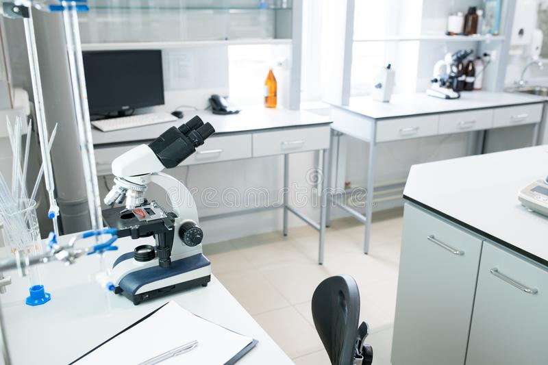 Modern Laboratory in Clinic. Microscope on table in empty science laboratory, copy space stock photo