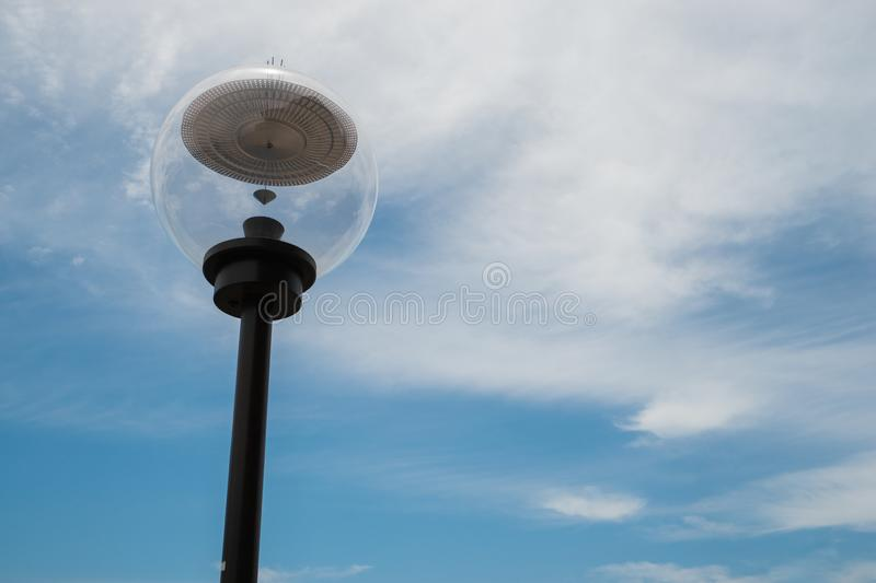 Modern lamp post against a blue cloudy sky stock images