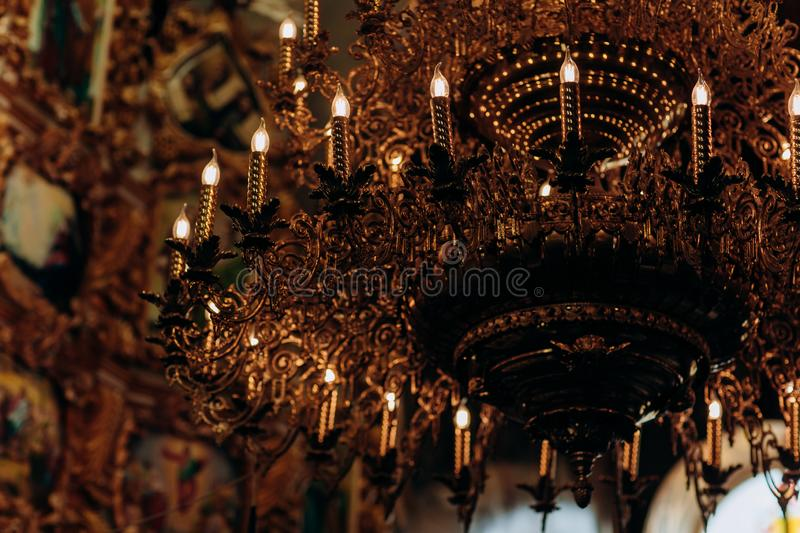 Gold-plated chandelier hangs in the old church near the icons. Modern lamps are like candles. stock images