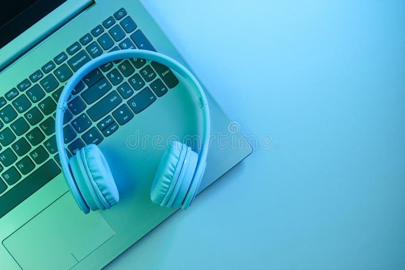 Modern laptop, wireless headphones. Gadgets. Neon night light, ultraviolet. Top view, minimalism. Modern laptop, wireless headphones. Gadgets. Neon night light stock image
