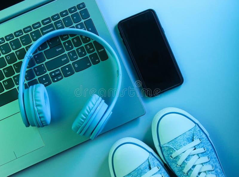 Modern laptop, wireless headphones, smartphone, sneakers. Gadgets. Neon night light, ultraviolet. Top view, minimalism stock photos