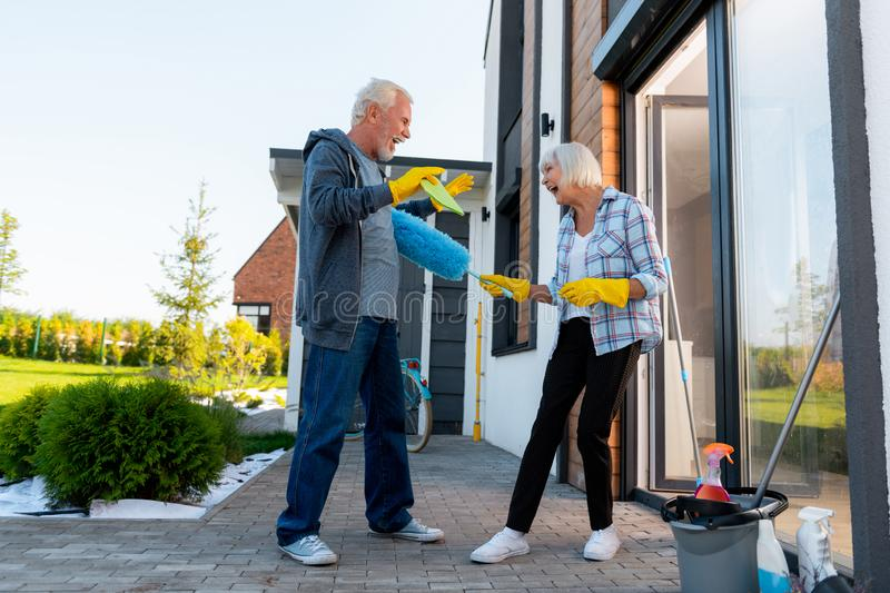 Modern laughing grandmother and grandfather having fun cleaning territory royalty free stock images