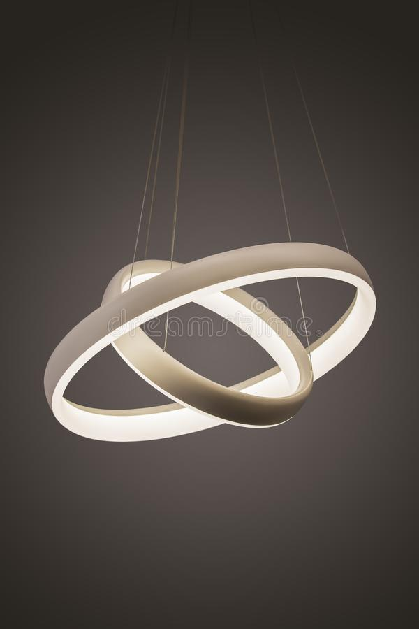 Modern led pendant light lamp illuminated, fashionable designer chandelier in the form of rings royalty free stock image