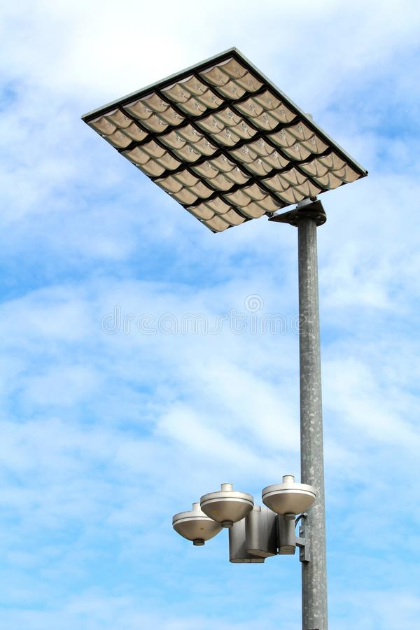 Modern LED street light reflectors in protective case pointed towards large reflective panels mounted on top of strong metal pole stock photo