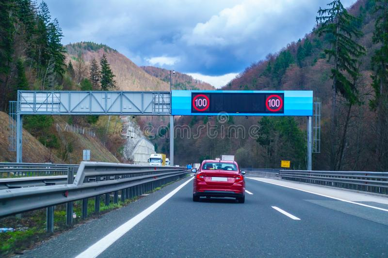 Modern LED traffic signs on highway, red car, truck on road. Modern LED traffic signs on Slovenian highway A1 near Trojane, red car, truck on road stock photos